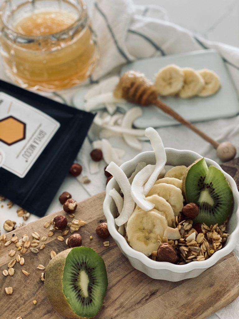 Granola z orzechami podana w misce wraz z świeżymi owocami i jogurtem